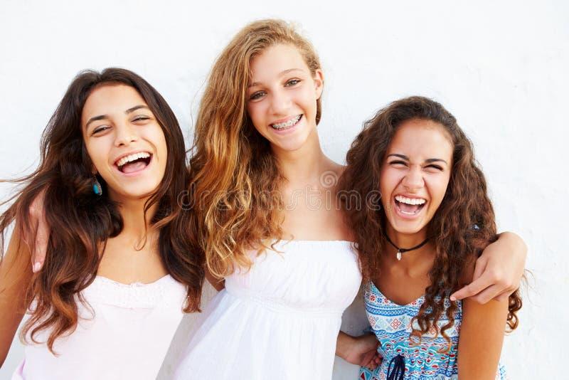 Un ritratto di tre adolescenti che pendono contro la parete immagine stock