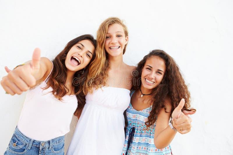 Un ritratto di tre adolescenti che pendono contro la parete immagini stock