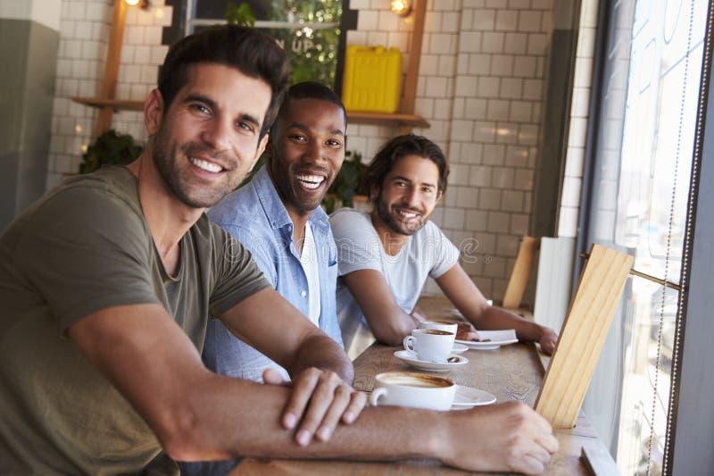 Un ritratto di tre amici maschii che si incontrano nella caffetteria immagini stock