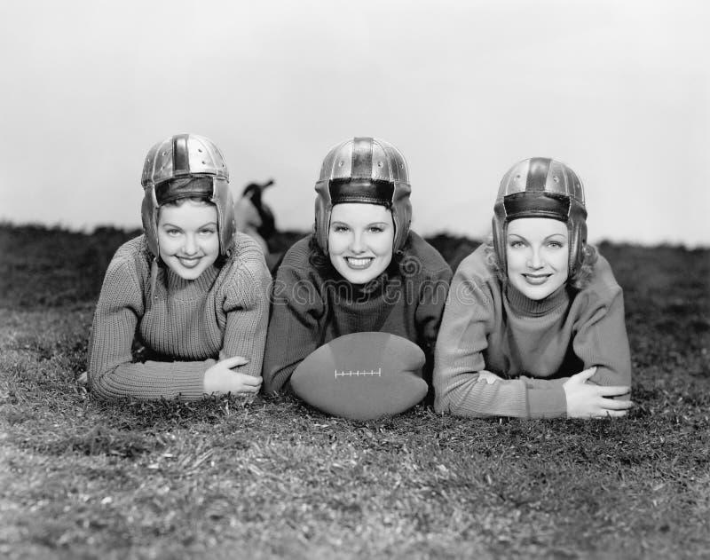 Un ritratto di tre donne nei caschi di calcio (tutte le persone rappresentate non sono vivente più lungo e nessuna proprietà esis fotografia stock libera da diritti