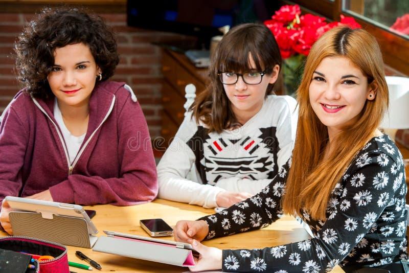 Un ritratto di tre giovani studentesse allo scrittorio. fotografie stock