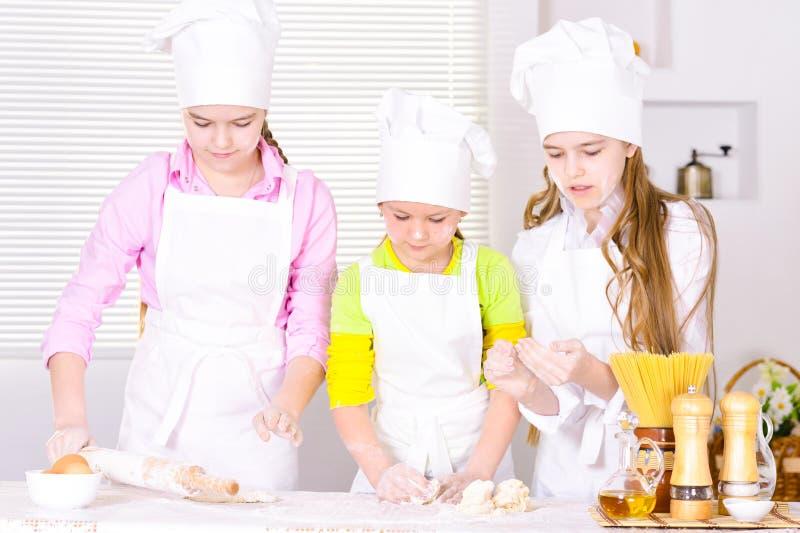 Un ritratto di tre ragazze sveglie che cucinano sulla cucina immagini stock libere da diritti