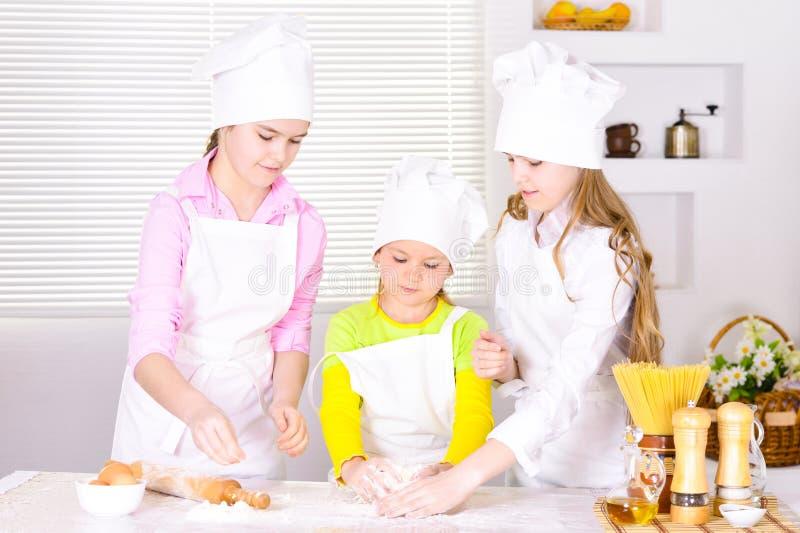 Un ritratto di tre ragazze sveglie che cucinano sulla cucina fotografia stock libera da diritti