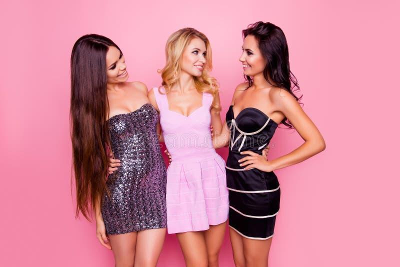 Un ritratto di tre svegli, ragazze piacevoli, esili, attraenti, in brevi vestiti, guardando l'un l'altro, divertendosi sul partit fotografie stock