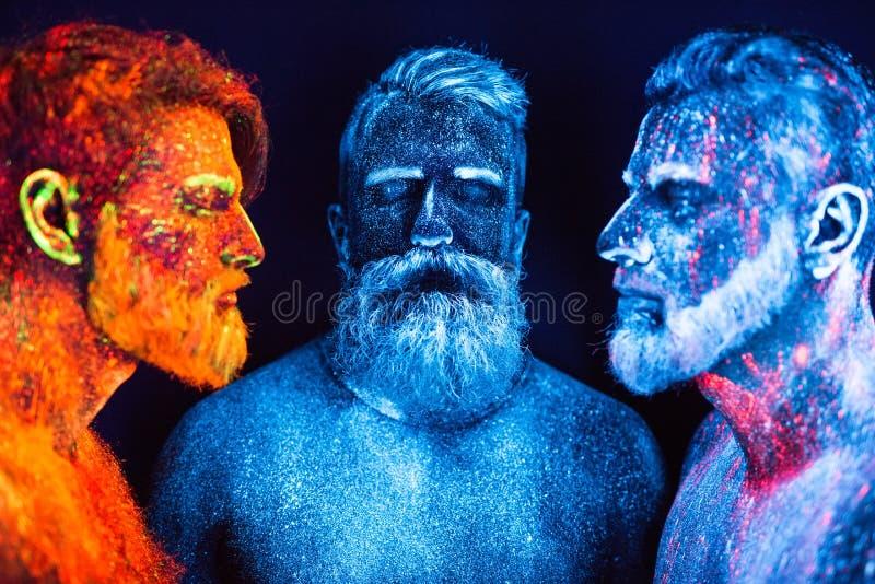 Un ritratto di tre uomini barbuti dipinti in polveri fluorescenti immagini stock
