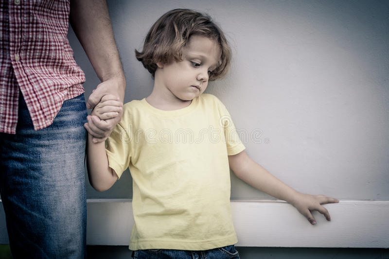 Un ritratto di un figlio triste che abbraccia suo padre fotografie stock libere da diritti
