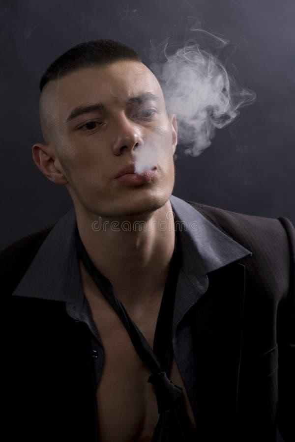 Un ritratto di un giovane che fuma una sigaretta fotografie stock