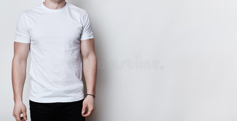 Un ritratto di un uomo che ha ente atletico che porta maglietta bianca in bianco che sta sul fondo bianco con lo spazio della cop immagini stock