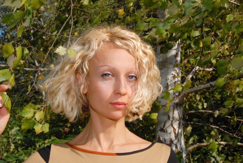 Un ritratto di una giovane donna piacevole con i capelli biondi ricci e i eys blu, stante vicino ad una betulla e tenente un ramo immagini stock