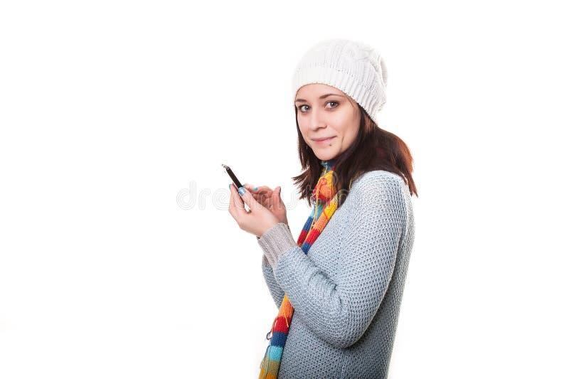Un ritratto di una persona che invia un messaggio dal telefono cellulare su fondo isolato fotografia stock libera da diritti