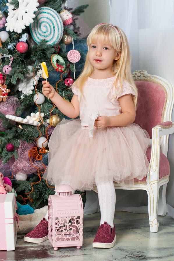 Un ritratto di una piccola ragazza bionda sveglia caucasica con le lecca-lecca colorate nella stanza festiva dello studio del nuo immagine stock
