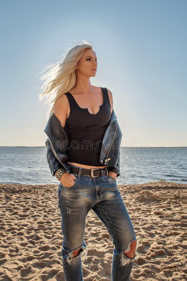 Un ritratto di una ragazza bionda audace in una maglietta aderente e nei jeans lacerati che stanno sulla spiaggia sabbiosa del ma fotografia stock
