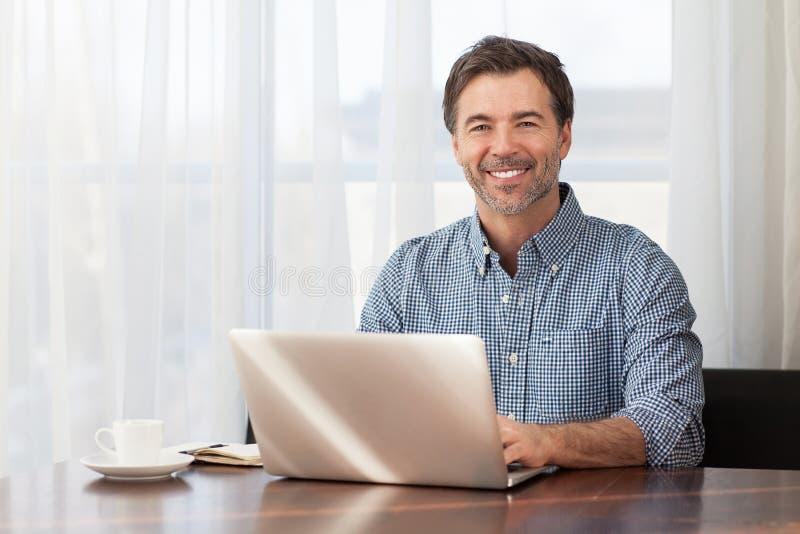 Un ritratto di un uomo barbuto di mezza età sorridente ad uno scrittorio fotografia stock