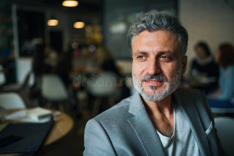 Un ritratto di un uomo d'affari maturo che si siede in un caffè Copi lo spazio fotografie stock libere da diritti