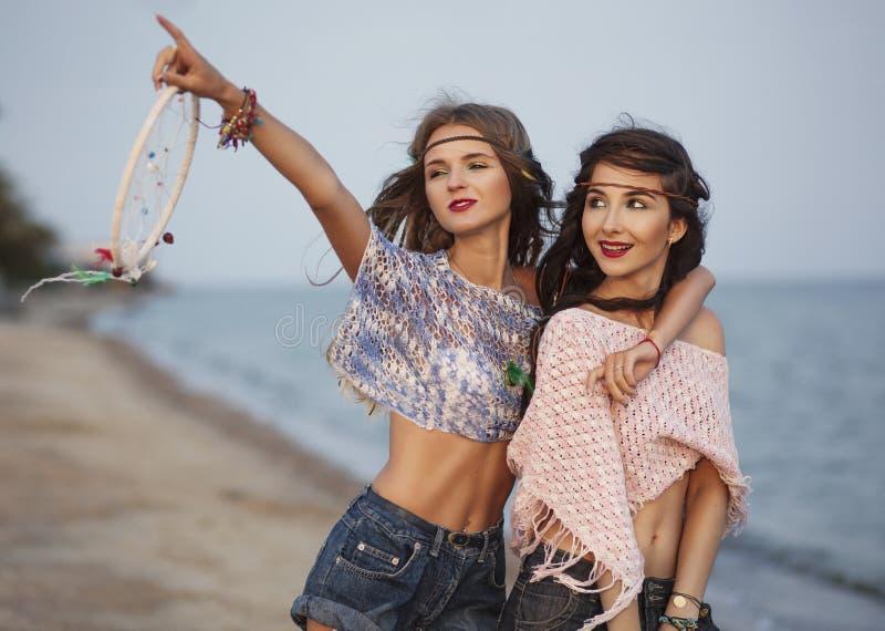 Un ritratto felice della donna di boho di due giovani al mare che mostra al fotografia stock libera da diritti