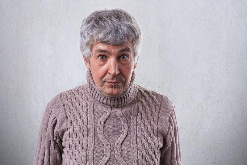 Un ritratto orizzontale dell'uomo bello senior che sta contro il maglione d'uso della parete bianca che guarda con la stupefazion fotografie stock libere da diritti