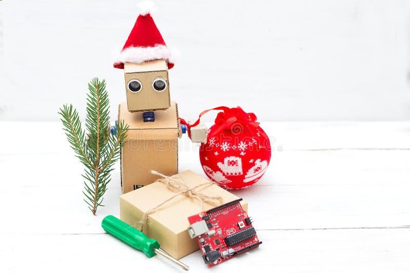 Un robot en un sombrero de santa lleva a cabo una rama de un árbol de navidad y de una a imágenes de archivo libres de regalías
