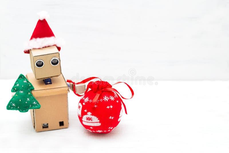 Un robot en un sombrero de santa sostiene un árbol de navidad y un juguete de la Navidad Copie el espacio fotografía de archivo libre de regalías