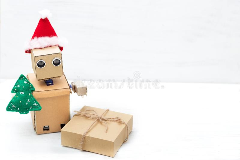 Un robot en un sombrero de santa sostiene una caja del árbol de navidad y de regalo copia fotografía de archivo