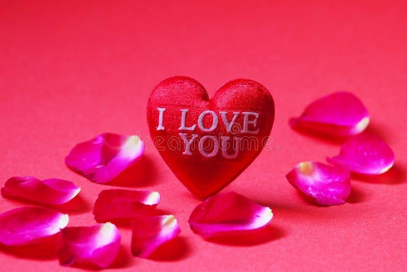 Un rojo en forma de corazón con los pétalos te amo y de Rose en fondo rojo fotografía de archivo libre de regalías