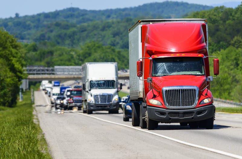 Un rojo semi lleva una línea de tráfico abajo de una carretera nacional en Tennessee fotos de archivo