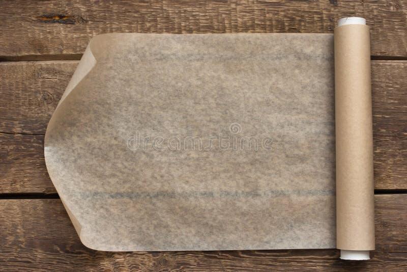 Un rollo abierto del documento sobre el fondo de madera de la tabla fotos de archivo libres de regalías