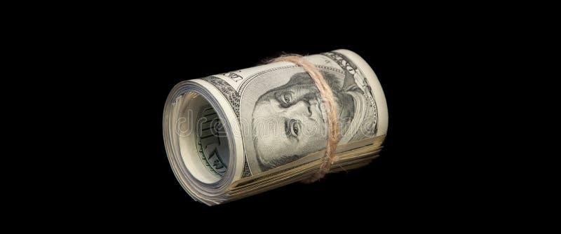 Un rollo de cientos billetes de dólar atados con una cuerda En un fondo negro Aislado imagen de archivo