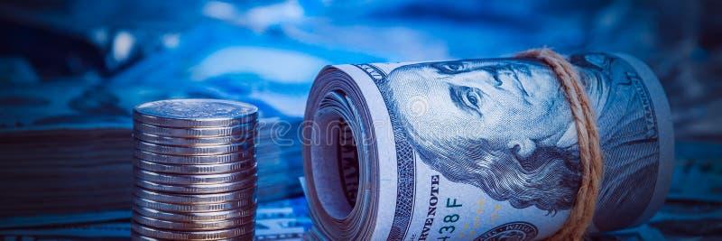 Un rollo de dólares con las monedas en el fondo de dispersado cientos billetes de dólar en luz azul fotos de archivo