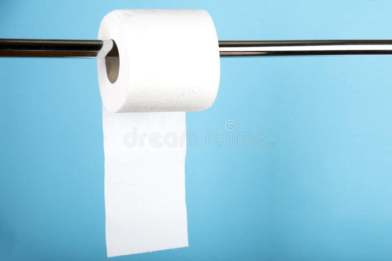 Un rollo del papel higiénico blanco en un fondo coloreado fotografía de archivo libre de regalías