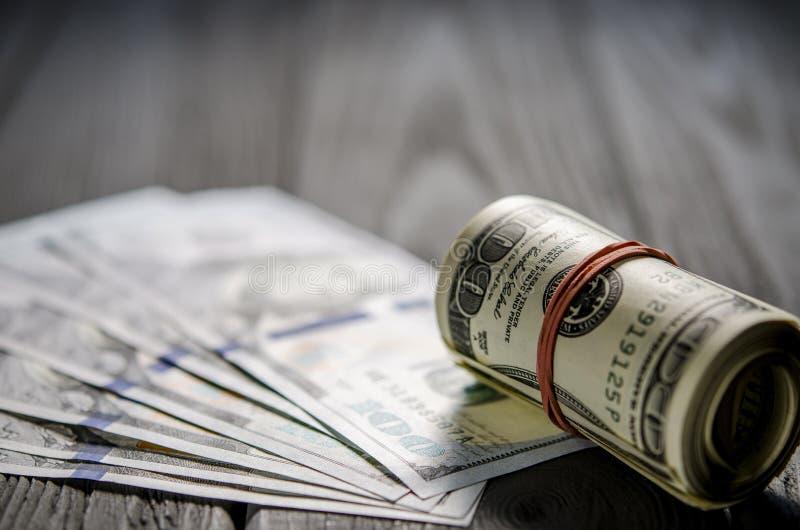 Un rollo grueso de los cientos billetes de banco viejos del d?lar at? una goma roja miente en la barba de nuevos cientos billetes fotografía de archivo libre de regalías