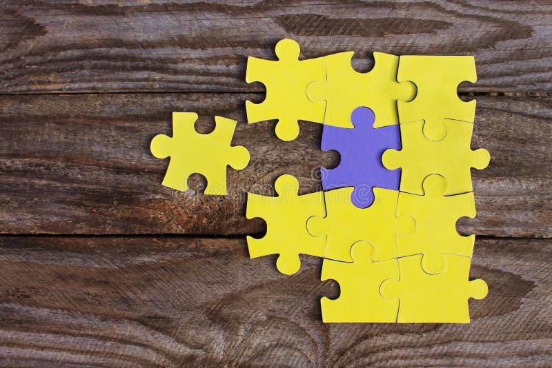 Un rompecabezas púrpura y muchos rompecabezas amarillos imágenes de archivo libres de regalías