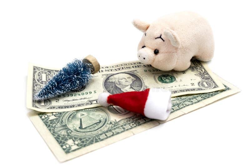 Un rosa guarro, un sombrero rojo de Santa Claus, un recuerdo del juguete del árbol de navidad en dos cuentas del 1 E.E.U.U. El co imagenes de archivo