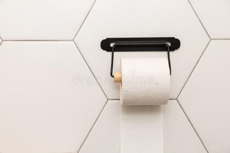 Un rotolo bianco della carta igienica molle che appende ordinatamente su un supporto moderno del cromo su una parete leggera del  immagine stock libera da diritti