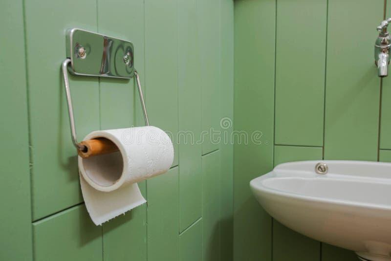Un rotolo bianco della carta igienica molle che appende ordinatamente su un supporto moderno del cromo su una parete verde del ba immagini stock