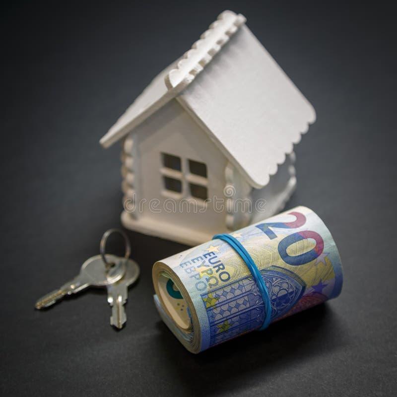 Un rotolo che consiste degli euro, di un modello della casa di colore bianco e delle chiavi ad una casa futura su un fondo nero fotografia stock libera da diritti