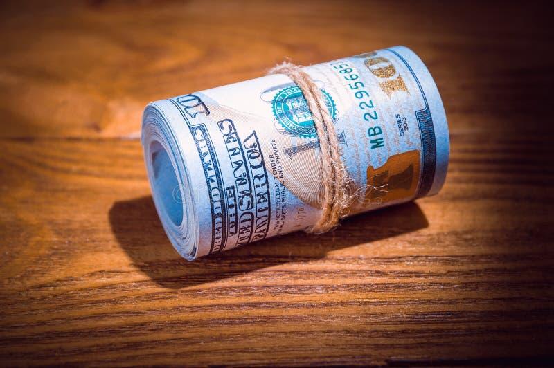 Un rotolo dei dollari su una tavola strutturata di legno nello scuro illuminato da un raggio di luce immagine stock