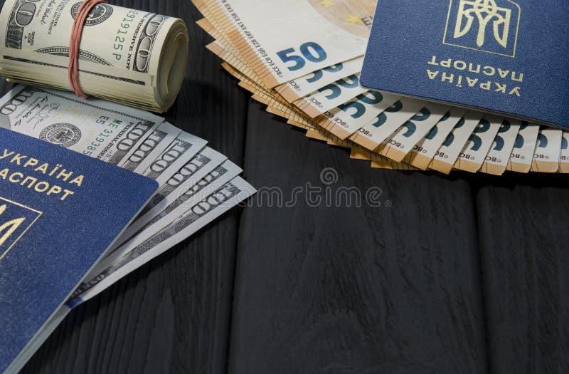 Un rouleau épais de vieux cent billets d'un dollar attachés avec une bande élastique rouge se trouve à côté des passeports biomét images stock