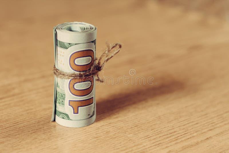 Un rouleau de cent billets d'un dollar sur un fond brun clair images stock