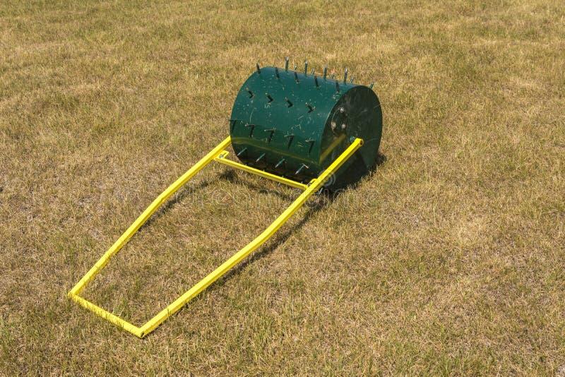 Un rouleau spécial pour la manipulation et la pose de la pelouse photo libre de droits