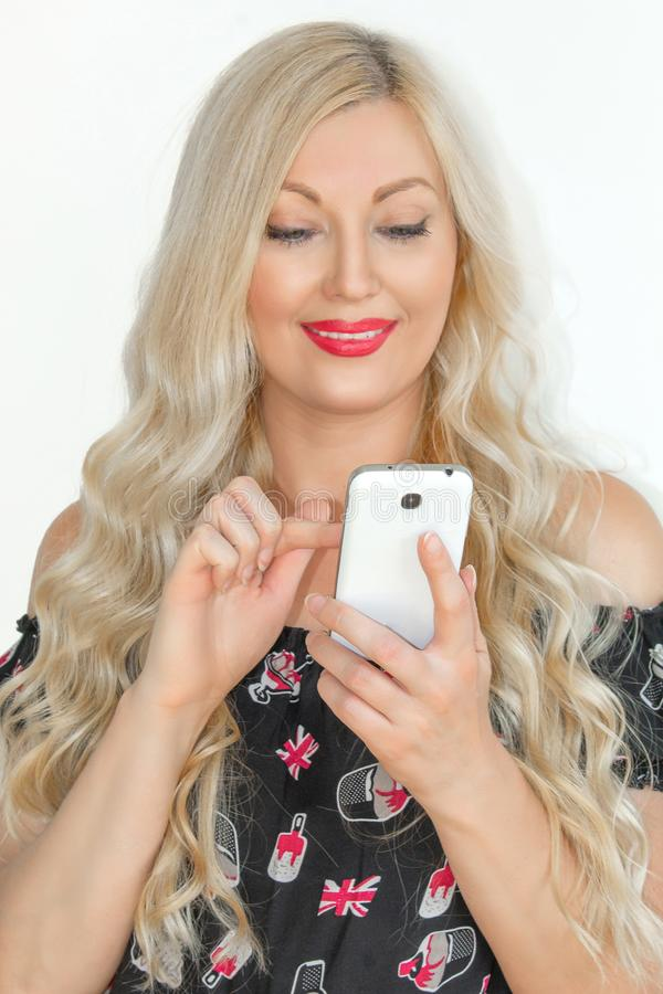 Un rubio joven hermoso con el pelo largo que juega en un teléfono móvil y una sonrisa lindos, en un fondo blanco El concepto de a imágenes de archivo libres de regalías