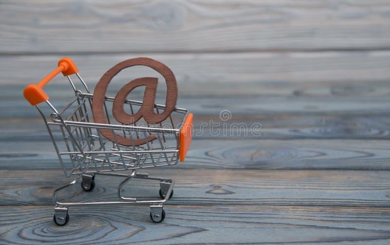 Un símbolo del email, carro de la compra en un fondo de madera del tablero foto de archivo libre de regalías