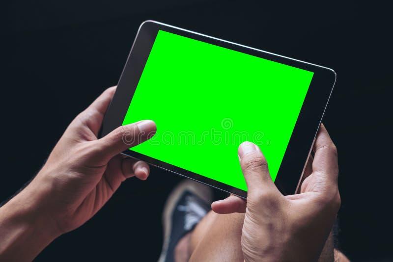 Un ` s d'homme remet tenir le PC noir de comprimé avec l'écran vert vide sur la cuisse à l'arrière-plan noir photos libres de droits