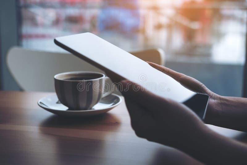 Un ` s de la mujer da sostener y usar la PC de la tableta con la taza de café en la tabla de madera con el fondo de la falta de d foto de archivo