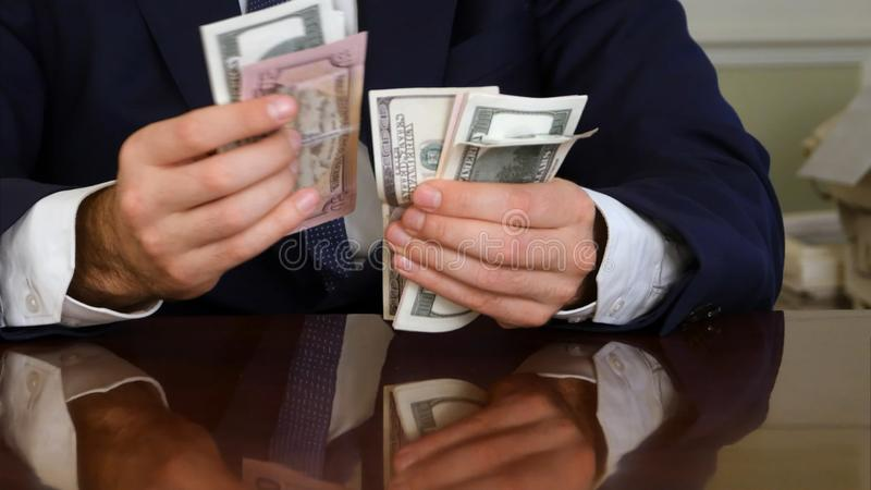 Un ` s del hombre de negocios da la cuenta de cientos billetes de dólar en una tabla fotografía de archivo libre de regalías