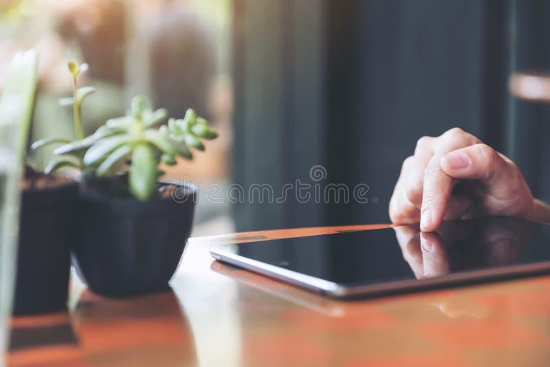 Un ` s della donna passa indicare, il contatto e per mezzo del pc della compressa con il vaso dell'albero sulla tavola immagini stock