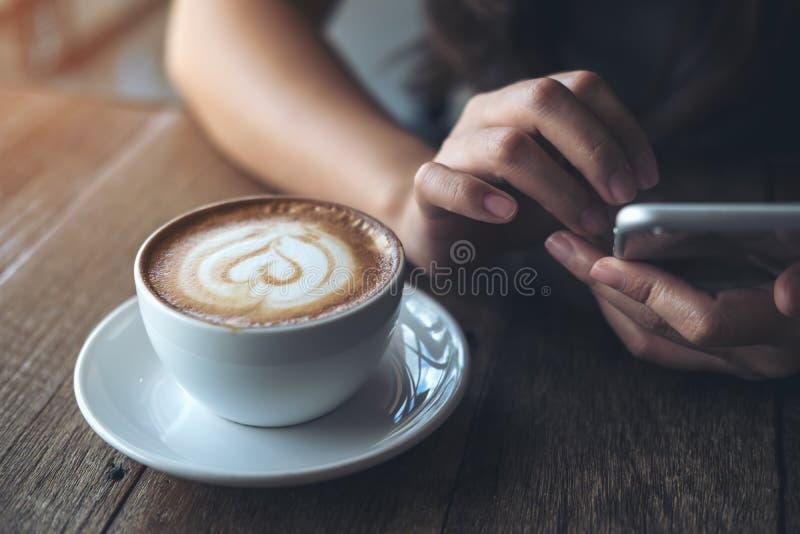 Un ` s della donna passa la tenuta, utilizzando ed indicando allo Smart Phone con la tazza di caffè del latte sulla tavola di leg fotografia stock