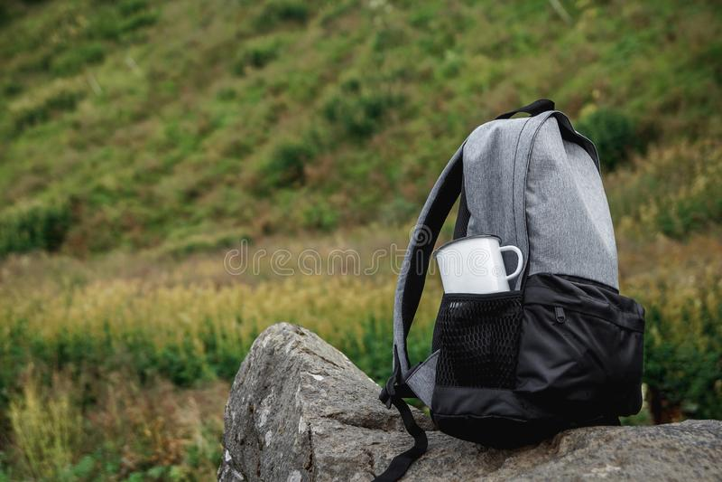Un sac à dos, une tasse, un bloc-notes et une carte se trouvent sur l'herbe Équipement de touristes La pomme se situe dans la poc photo libre de droits