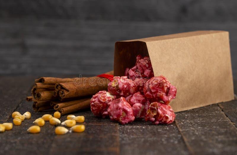 Un sac de maïs éclaté rouge foncé de cannelle sur une table de cuisine en bois image libre de droits