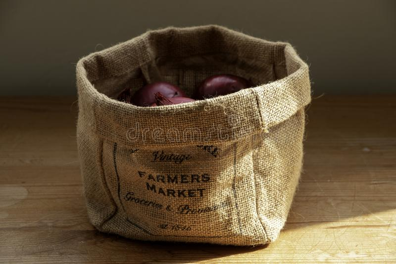 Un sac du marché d'agriculteurs des oignons photos stock
