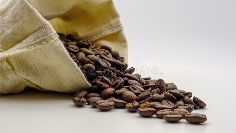 Un saco con los granos de café asados en el fondo blanco fotos de archivo